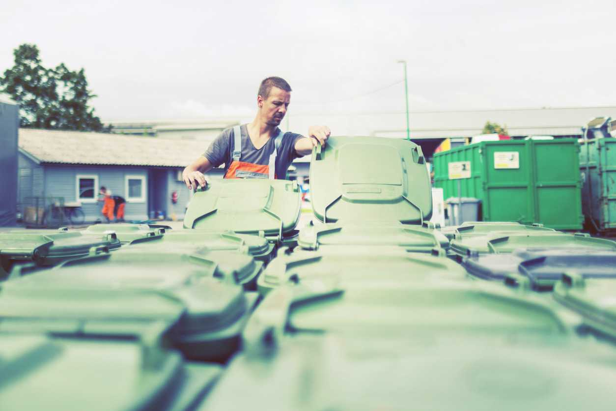 Man working at a large trash and recycling center